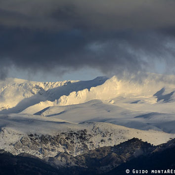 Snowy mountains through the clouds. by Guido Montañés
