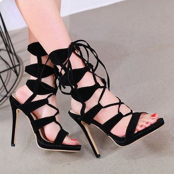 Black suede sandals with strappy toe slip and ultra high heels