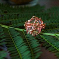Copper wire ring molded around a pink glass stone