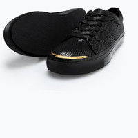 Sneakers with gold metal in the toe