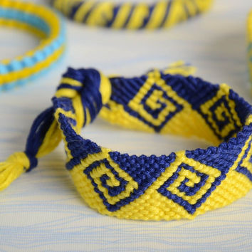 Handmade wide friendship wrist bracelet woven of yellow and blue embroidery floss