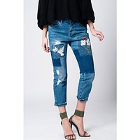 Jeans with cloth and embroidered floral patches