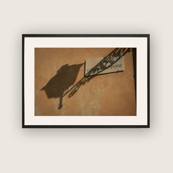 Colour photograph of a street lamp casting a shadow on a burnt umber wall in Florence,  Monochromatic Art, Loft Wall Art, Travel Photography