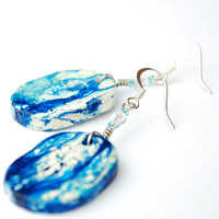 Oval shaped white and blue earrings with abstract pattern. Expressive statement jewelry.