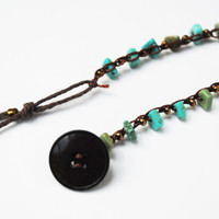 Turquoise bead crocheted bracelet with upcycled beads and clasped by a lucite vintage button