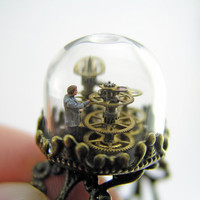 Steampunk glass dome ring. Miniature little man working amidst machinery made out of tiny cogs and gears