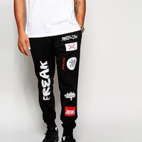 ASOS Skinny Sweatpants With All Over Badge Designs at asos.com