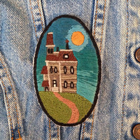creepy house patch hand embroidered hand stitched mansion on a hill at sunset glowing