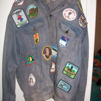 Vintage todays news jean jacket with patches on it.