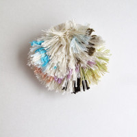 Fiber art brooch hand embroidered on cream muslin using cotton threads in blue, peach, lavender, greens and browns on sturdy cream felt back