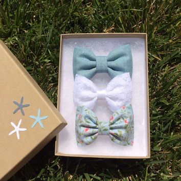 Textured teal, pale blue floral, and white lace hair bows from seaside sparrow.  Seaside Sparrow bows make the perfect birthday gift.