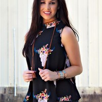 Our More Than You Deserve Tunic Top is a must have this season! It's a sleeveless tunic top with bullhead skull print and flowers. Mock neck with keyhole with button closure. This top is lined.
