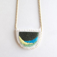 Hand embroidered necklace on matte gold tone ball chain with abstract design of greens, yellow and blue colors An Astrid Endeavor