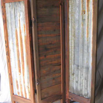 Screen made from reclaimed wood from a barn, and corrugated steel roofing.
