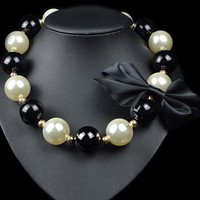 Beady Luxury Oversized Pearl Necklace with Black Bow Finish