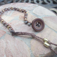 boho style crochet bracelet with upcycled vintage blue stone beads and gold beads and a vintage button tassel