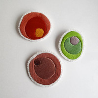Hand embroidered brooch set of three geometric spheres in tan, red and green on cream muslin with cream felt backing Modern embroidery
