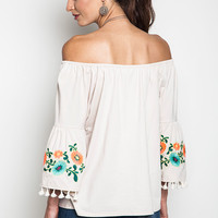 This super cute off shoulders top featuring three quarter bell sleeves with embroidery floral and tassel detailing. Unlined.