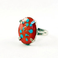 Silver Colored Ring With Blue Polka Dots On a Red Resin Background