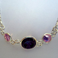 Sterling silver bracelet with purple cubic zirconia in center and pink zirconia on either side.
