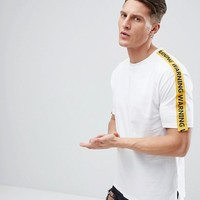 Bershka Taped Sleeves Warning Slogan T-Shirt With Uneven Hem In White at asos.com