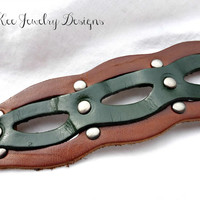 Leather cuff bracelet with metal adjustable wrist clasp. Dark green and brown leather.