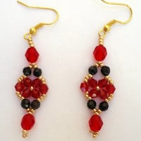 Beaded earrings in flower pattern with ruby crystals,black rondells,gold Miyuki seed beads and fire mountain gems. Handmade