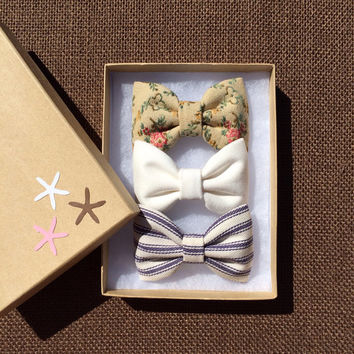 Textured floral, winter white, and navy pinstripe hair bows from seaside sparrow. Perfect gift for any occasion.