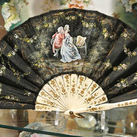 Silk Fan French Hand Painted Black Silk Fan Celluloid Carved Gold Floral Handle Lovers Garden Scene Circa 1940s Made In France Work of Art