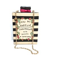 """Add some elegance to your look with Betsey's Parfum-shaped silhouette handbag, featuring cream/black stripe print throughout and """"EAU DE PARFUM CHAMPAGNE AND ROSES BY BETSEY JOHNSON"""" written on front. Push lock closure with fuchsia color bow detailing, and"""