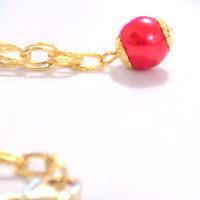Gold necklace with a red pearl