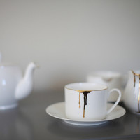 Drip Tease cup and saucer in gold
