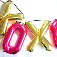 XOXO Valentine's day party decorations, mylar balloon banner in metallic gold and magenta.
